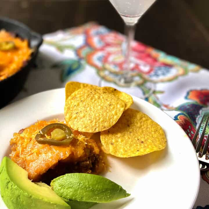 Tamale Pie on plate with sliced avocado and tortilla chips.