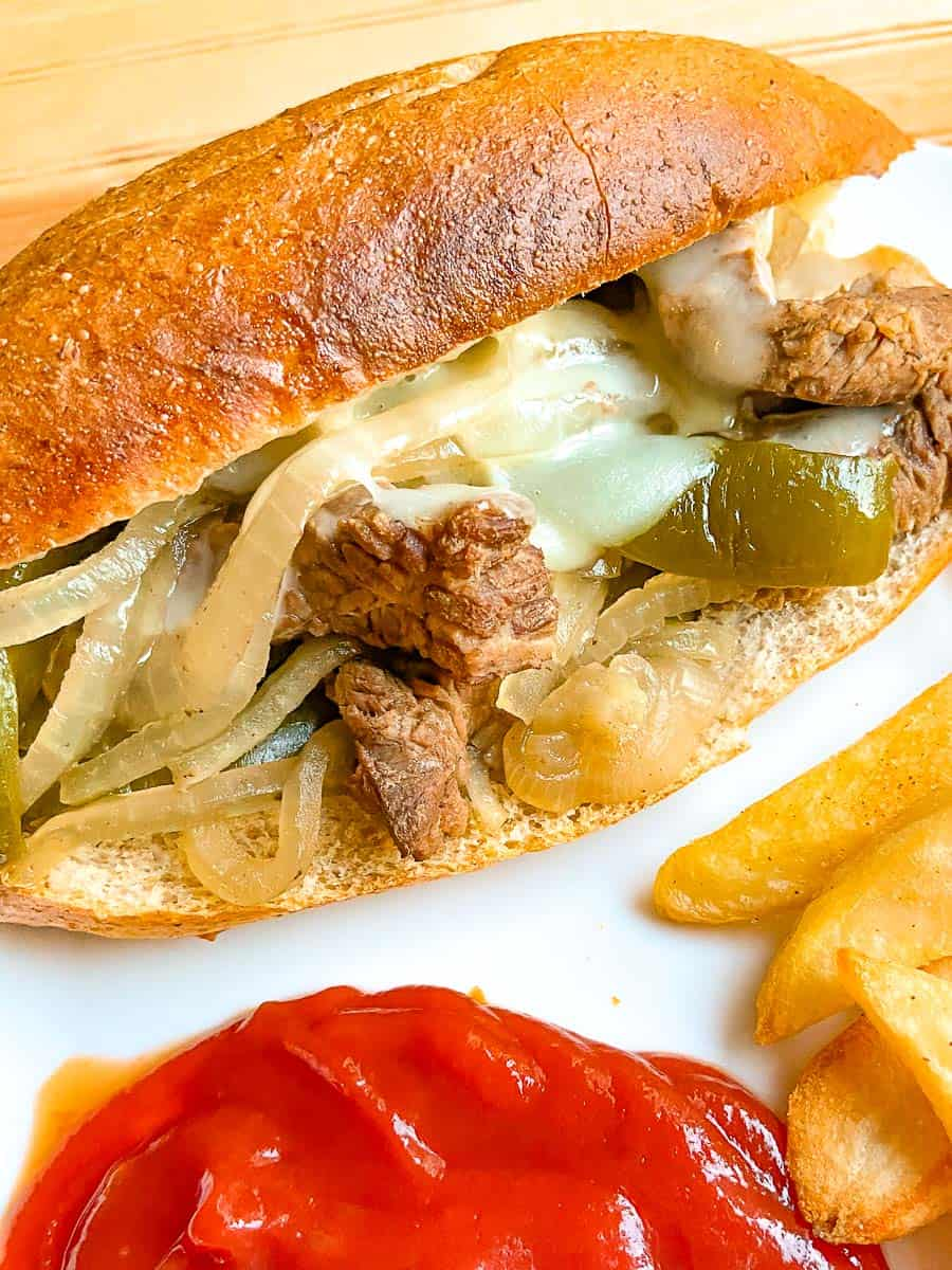 Philly cheesesteak and fries on white plate.