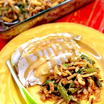 Green Bean casserole on gold plate with turkey and gravy.