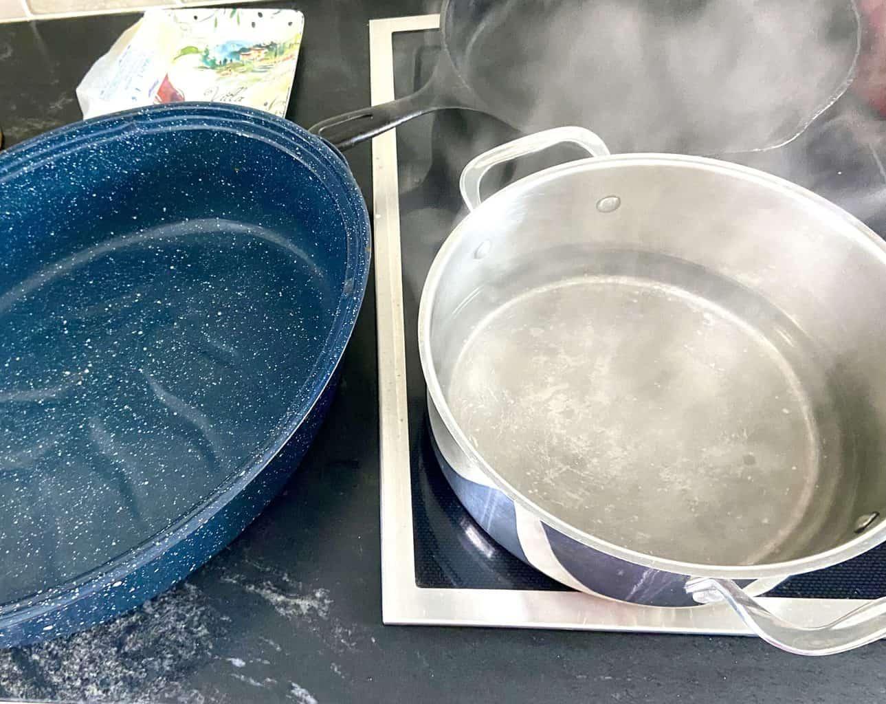 Roasting pan next to pot of boiling water.