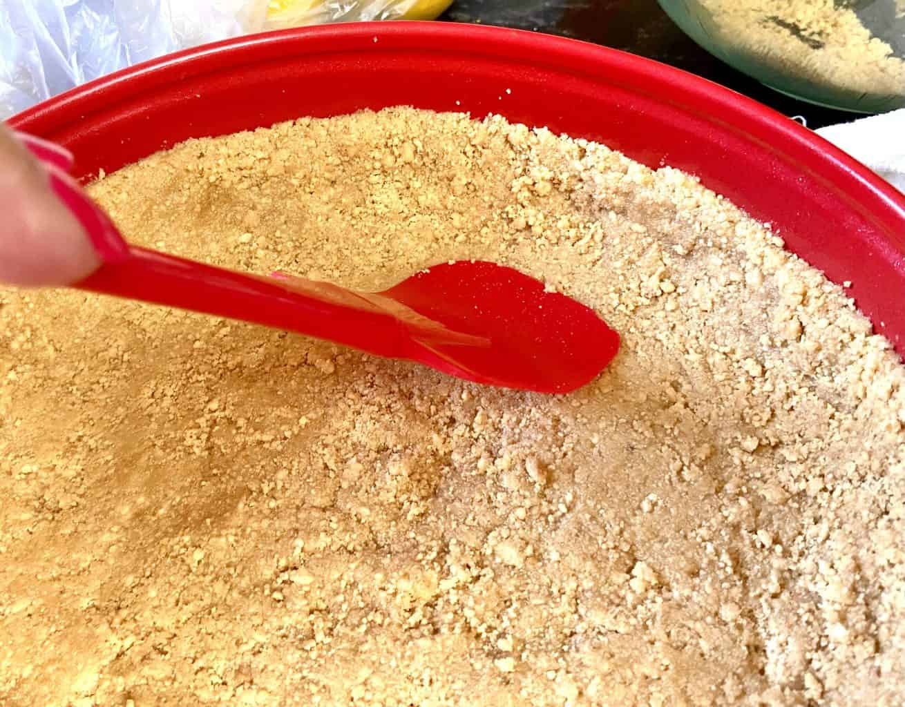 Graham cracker crust being pressed into pan with spatula.