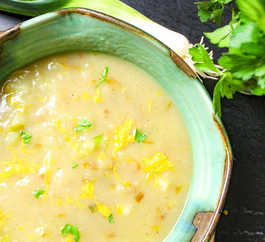 Vegan potato leek soup in greeen bowl garnished with parsley.