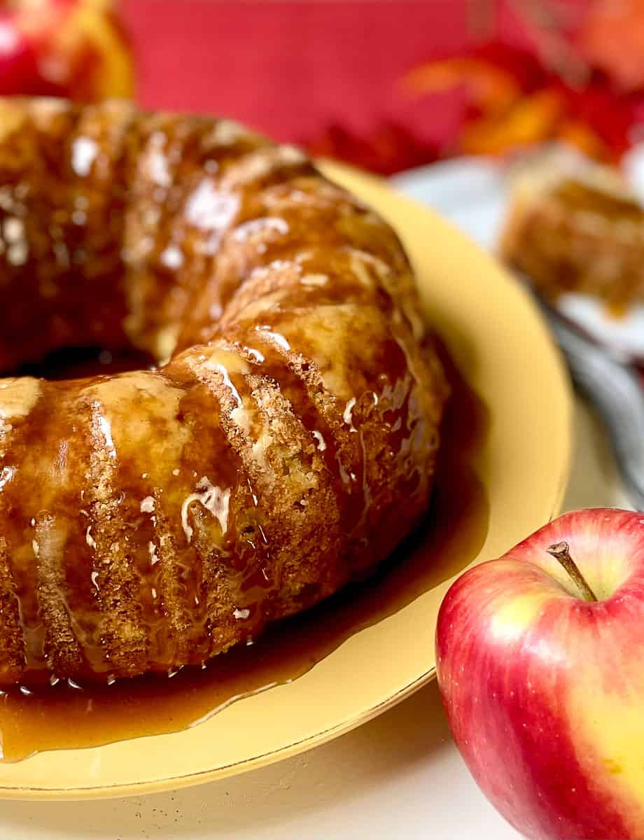 Apple cake with glaze on gold plate.