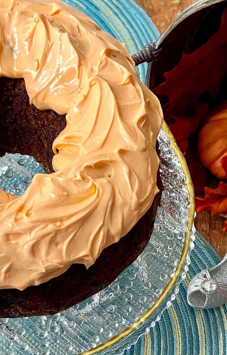 Cinderella cake with orange icing on crystal cake plate.