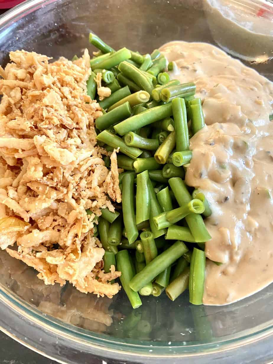 Fried onions, green beans and soup in bowl.