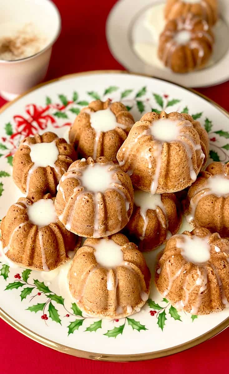 Mini eggnog cakes stacked on a decorative platter.