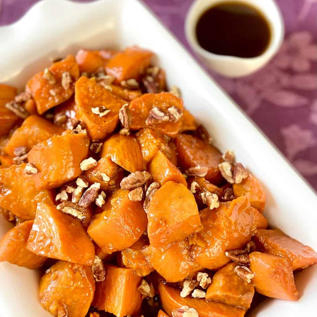Candied sweet potatoes in a rectangular serving platter.