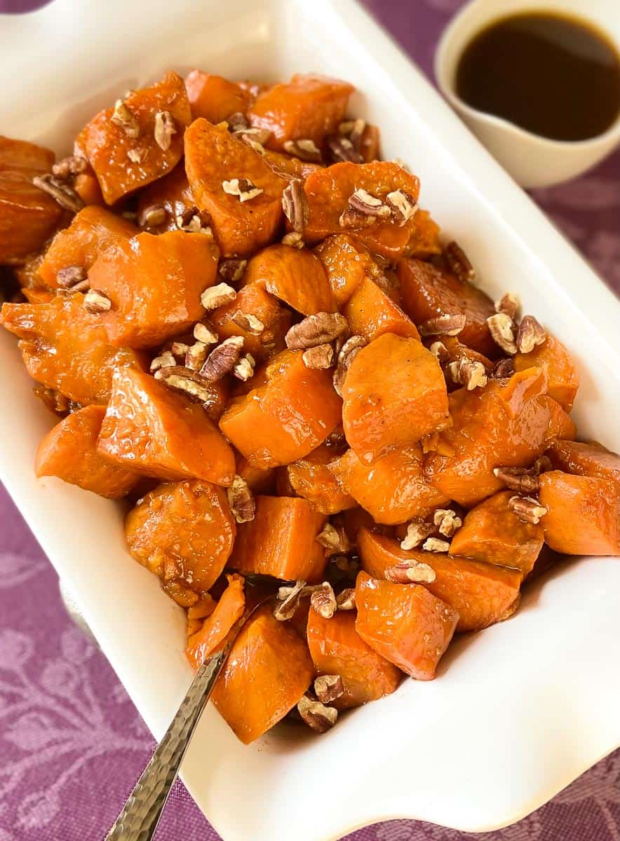 Candied sweet potatoes with chopped pecans in serving bowl.