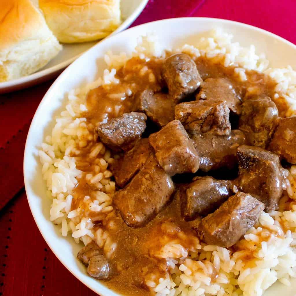 Beef tips, rice and gravy in white bowl.