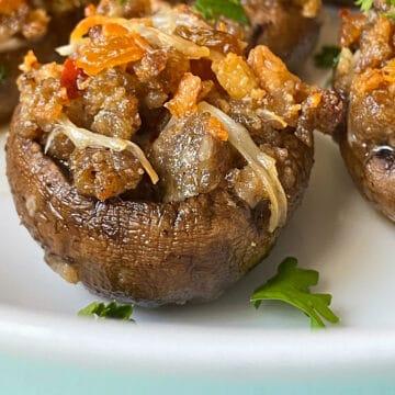 Sausage Stuffed Mushrooms on white plate.