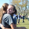 Freshman Maddie Wilson hugs her teammate after finishing the race. Photo by Grace Heitmann