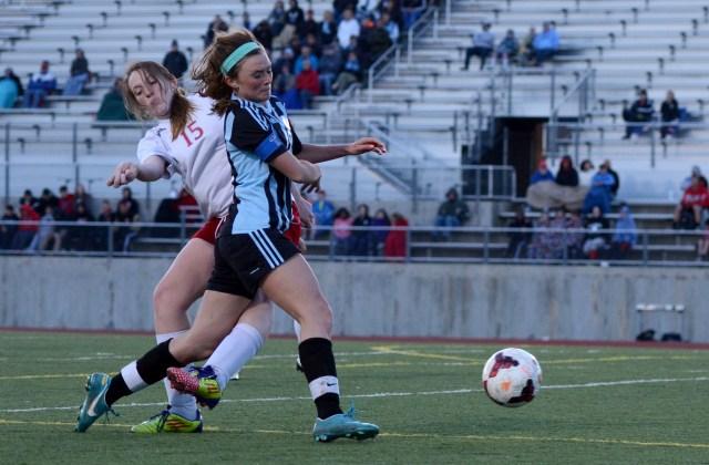 Junior Emma Braasch powers through opponent to reach the ball. By Katie Lamar