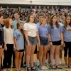 """Mr. Foley and the Chamber Choir sings """"Unwritten"""" to the students in the gym."""