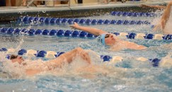Freshman Evan Root takes a lead in his heat receiving fourth place at a time of 58.00 seconds in the 100 yard Backstroke. Photo by Annie Lomshek.