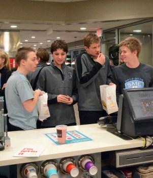 Teammates Bennett Hense, Aidan Holbrook, Hayden Lindscott, and Ian Longan snag some fries while waiting. Photo by Annie Lomshek.