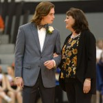Senior Clayton Phillips and his mother exchange smiles after walking onto the court during the crowning of the Sweetheart Queen. Phillips was crowned king at the dance Saturday.  Photo by Elizabeth Anderson