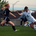 Sophomore Emily Cooper kicks the soccer ball as her opponent comes to kick it away from her. Photo by Katherine Odell