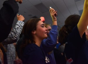 Junior Isabelle Cunningham, along with other students, holds up her phone flashlight and sway during juniors Sam Fay and Caroline Blubaugh's performance. Photo by Lucy Morantz