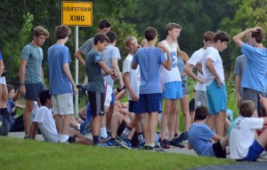 The boys cross country team stretches before they begin their race. Photo by Ally Griffith