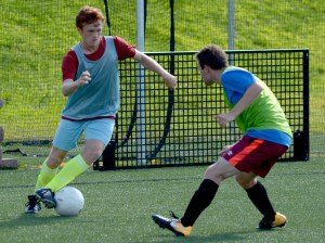 Senior Tommy Nelson attempts to get around his teammate Will Tulp during a scrimmage. Photo by Luke Hoffman