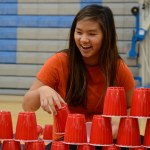 Quinci Cartmell laughs as she carefully stacks her cup pyramid for her team's dance. Photo by Kathleen Deedy