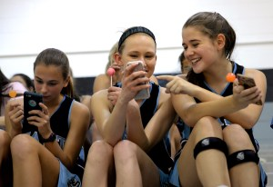 Sitting in the stands with freshman Paige Peugot, freshman Kelsey Christensen laughs as freshman Susie Green shows her her phone. Photo by Ellie Thoma