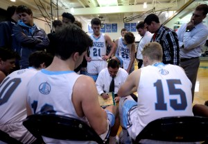 The team gathers around Coach Hair during a time out as he gives the team instructions. Photo by Ellie Thoma