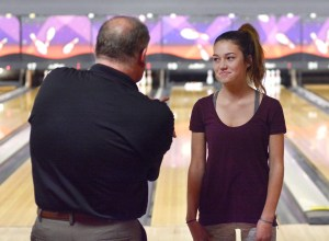 Coach Elliott demonstrates the correct technique to one of his bowlers, freshman Ariana Reck. Photo by Luke Hoffman