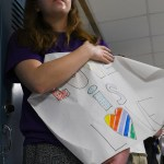 Senior Ellie Van Gorden holds poster to greet people in the morning. Photo by Carson Holtgraves