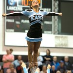Senior Astrid Cifuentes tops the a cheerleader's pyramid during halftime. Photo by Luke Hoffman