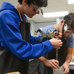 Kyle Battey and Max Rogler move the graduated cylinder into a holder. Photo by Kathleen Deedy