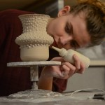 Senior Aeria Deemy puts the finishing touches on her clay pot. Photo by Kathleen Deedy