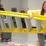 Seniors Julia Stopperan and Madeline Hlobik carry a ladder into the room to make it easier to hang up the ceiling decorations. Photo by Luke Hoffman