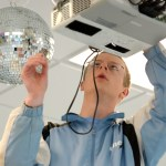 Senior Andrew Moore makes sure the disco ball is securely fastened to the ceiling. Photo by Luke Hoffman