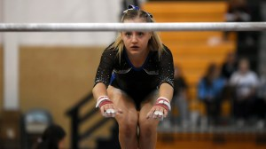 Senior Emily Eadens reaches for the bars during her uneven bars routine. Photo by Kate Nixon