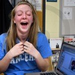 Senior Lilly Taylor laughs at the dog calendar she made for her dad for Christmas. Photo by Katherine McGinness