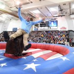 After spinning around backwards on a mechanical bull, assistant principal Britton Haney falls onto the padding. Photo by Grace Goldman