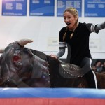 Trying to keep her balance, sophomore Kathryn Nachtigal laughs as she rides the mechanical bull. Photo by Megan Stopperan