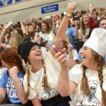Seniors Sarah Grimm and Hallie Higgason laugh as Grimm uses her watch flashlight to join the crowd in their chant. Photo by Luke Hoffman