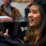 While watching a dance performance,  sophomore Quinci Cartmell smiles. Photo by Trevor Paulus