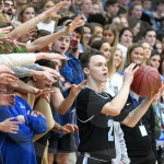 While the Rockhurst student section holds out their hands and yells, sophomore Tommy Dreyer looks for an open teammate to pass the ball to. Photo by Grace Goldman