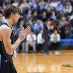 Senior Noah Kurlbaum claps after the East scores a basket in the first quarter. Photo by Lucy Morantz