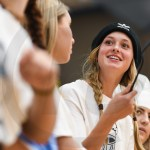 Senior Sarah Grimm talks to a student in the Rockhurst student section from across the bleachers. Photo by Lucy Morantz