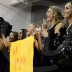 Sophomore Lauren Dirks and seniors Liddy Stallard, Hannah Goettsch, Olivia Caponecchi, and Gia Hense cheer as their teammate, senior Piper Noblit, walks into the gym during halftime with the other queen nominees. Photo by Julia Percy