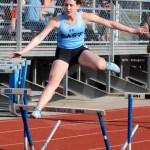 Junior Lizzie Macadam jumps over the hurdle but barely hits it on the way over. Photo by Megan Biles