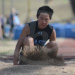 Sophomore Wen Clough lands in the sand while finishing the long jump. Photo by Noelle Griffin