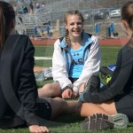 Sophomore Kelly McAlister sits with her friends right before the meet begins. Photo by Elle Karras