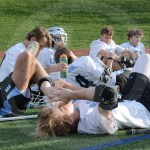 The team rests during halftime while the coaches talk about their performance. Photo by Noelle Griffin