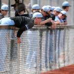 Junior Andrew Groat reaches over the fence to grab a foul ball. Photo by Julia Percy