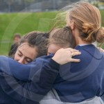 Sophomores Cameron Hughes, Macie Stump, and Phoebe Hendon hug and support each other before competing in a 100. Photo by Elle Karras